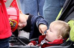 Little Boy Wearing a Firefighter Hat Feeding Baby Popcorn While the Baby Sits in a Stroller